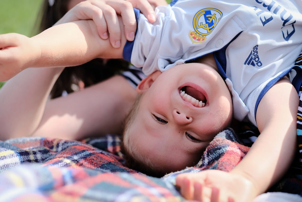 Boy upside down with his mother laughing on a sunny day