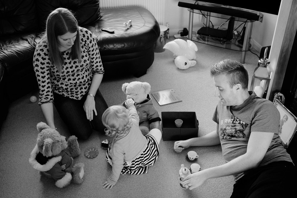 Documentary family photography capturing the whole family playing together. In black and white.