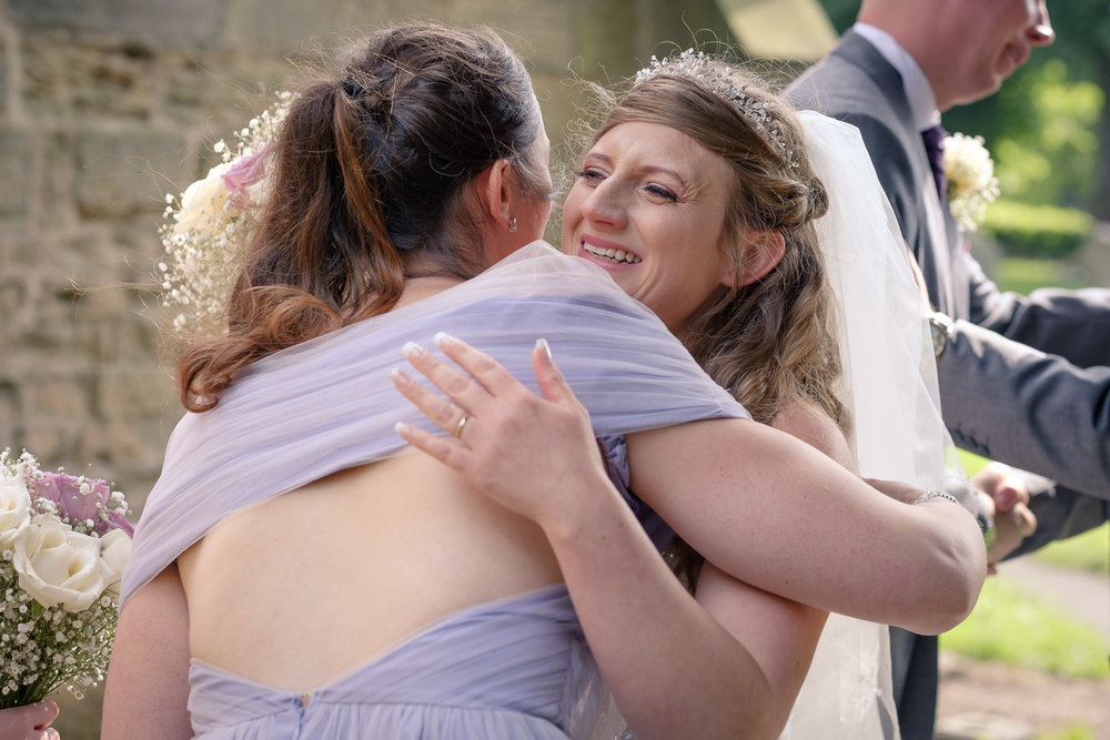 Nottingham-weddings-bridesmaid-congratulates-bride