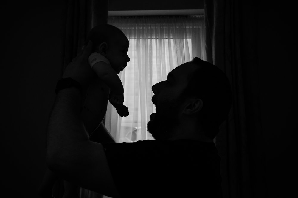 Silhouette of Dad holds up baby Finley during a documentary baby photoshoot.