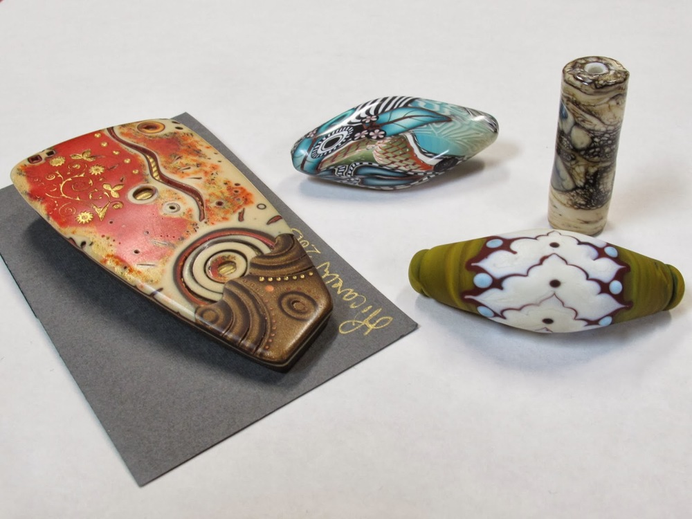 Clockwise from Left to Right: Polymer pendant by  Julie Picarello  of Yellow House Designs, polymer bead by  Klew Expressions , glass bead by  Michelle Davis  of Tangible Light Studio, and glass bead by  Terri Caspary Schmidt  of Caspary Lampwork.