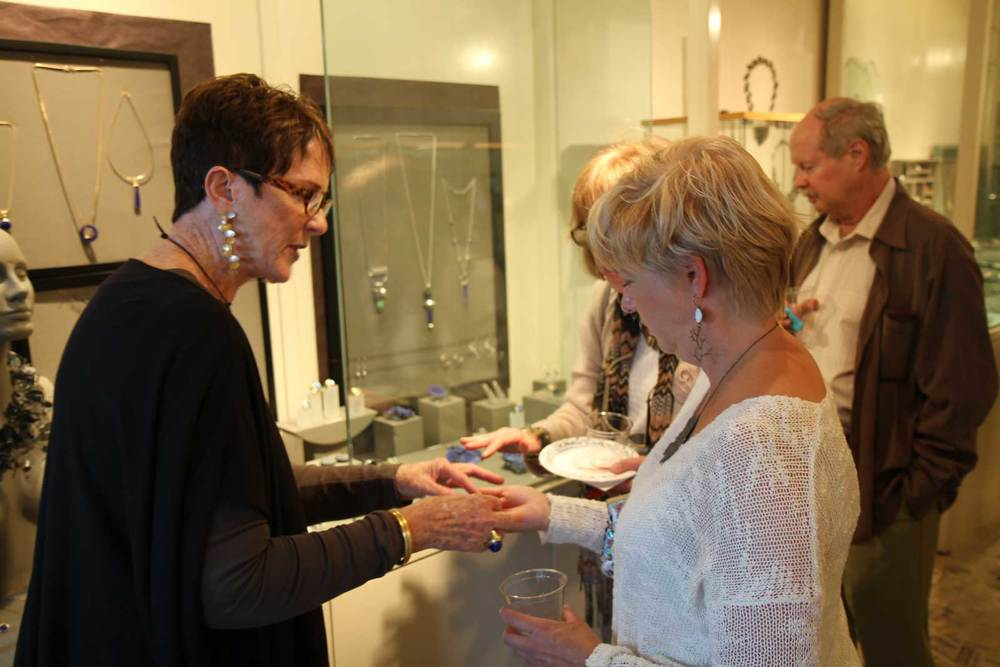 Gallery co-owner Jane Groover presents a piece of jewelry for a curious onlooker's appraisal.