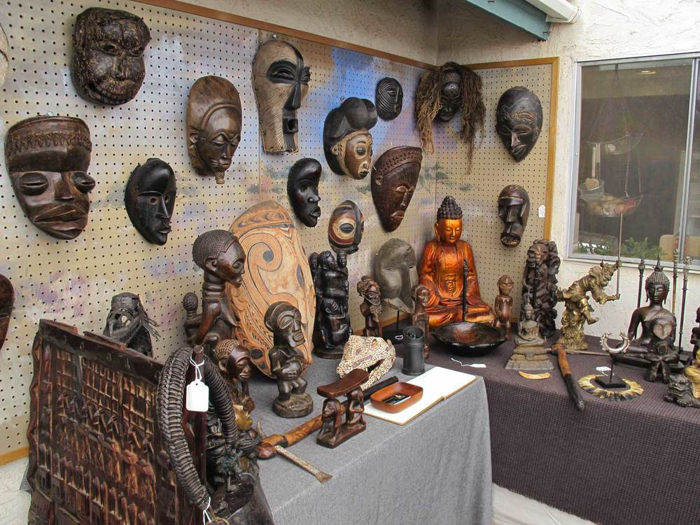 A variety of African masks, buddhist art and other sculpture in the collection of Geoffrey Logan.