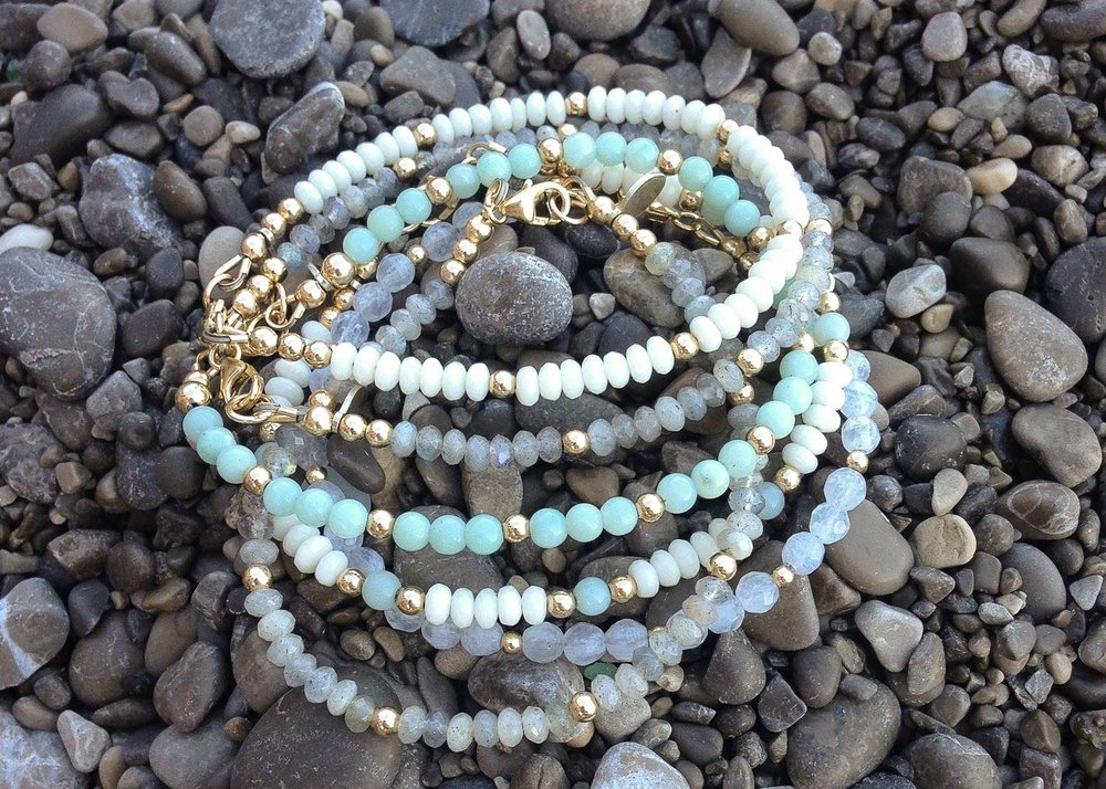 A thick stack of Visco bracelets resting on a Positano beach.