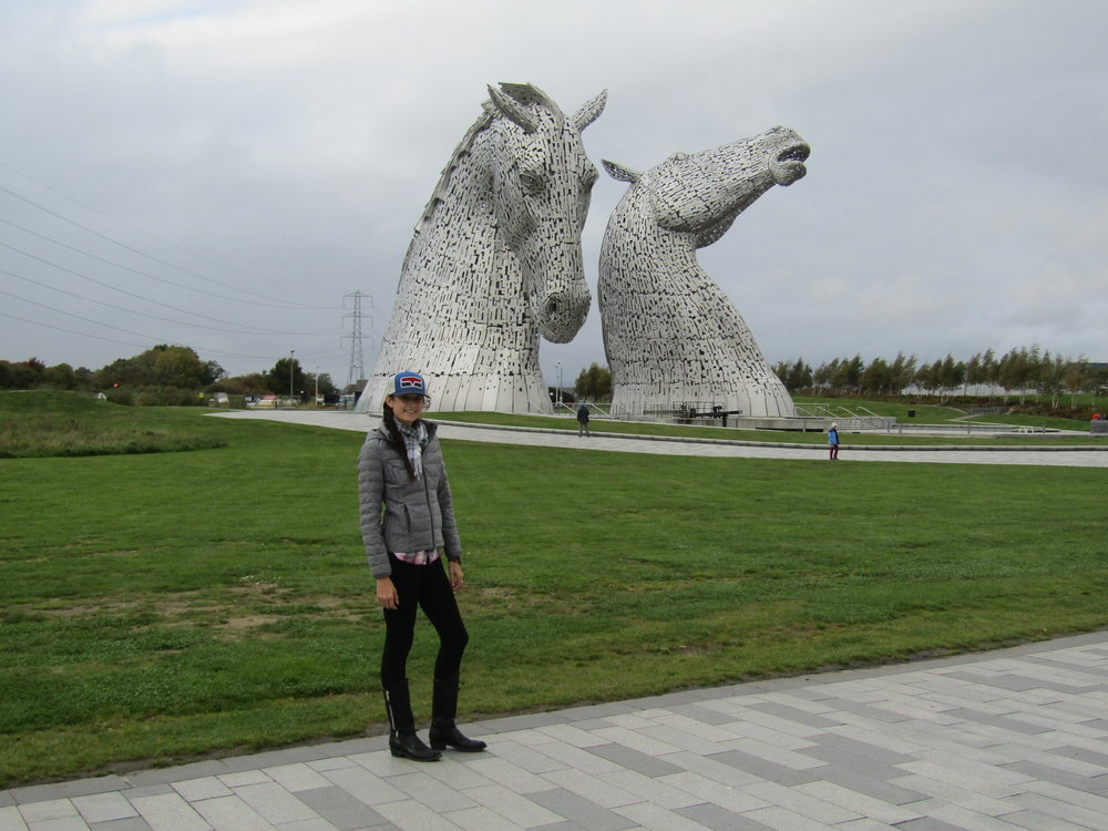 Checking out the Kelpies monument in Scotland in my leggings, Old Gringo boots, a warm jacket for the autumn air and my patriotic red-white-and-blue Kimes trucker cap.