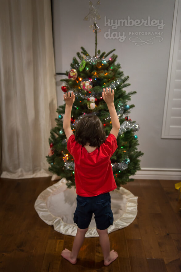 Boy in front of Christmas tree