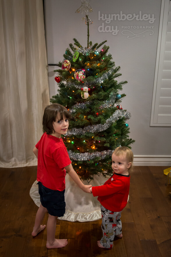 Brothers smiling in front of the Christmas tree while holding hands