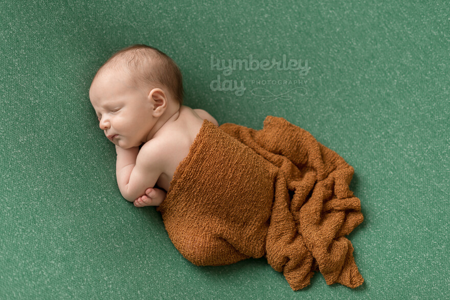 Baby boy on green backdrop with burnt orange wrap | Orange County newborn photographer