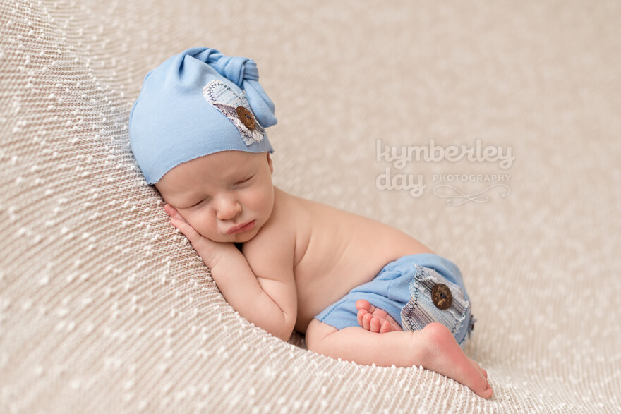 Baby with blue hat on brown backdrop | Orange County newborn photographer