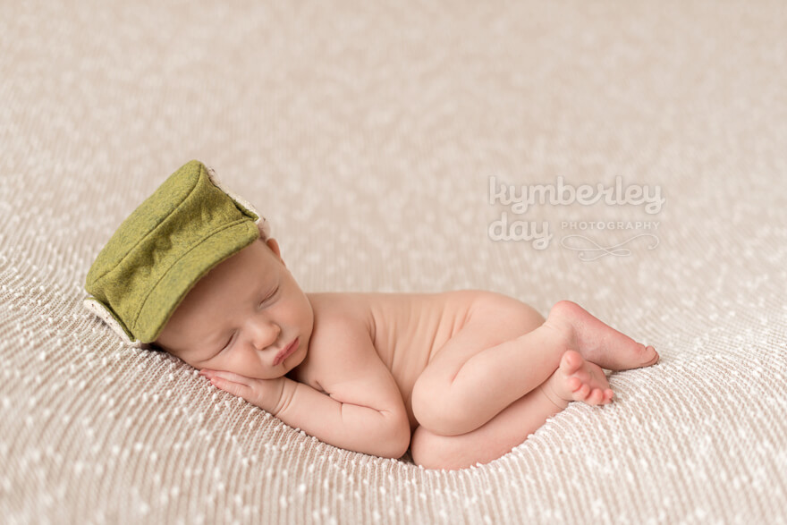 Baby with green Elmer Fudd hat on tan background | Orange County newborn photographer