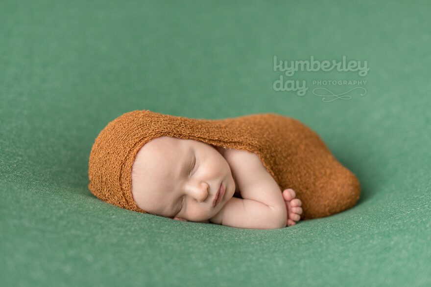 Baby with burnt orange egg wrap on green backdrop | Orange County newborn photographer