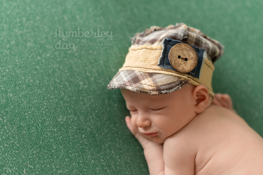 Orange County newborn photographer | baby smiling with brown baseball cap