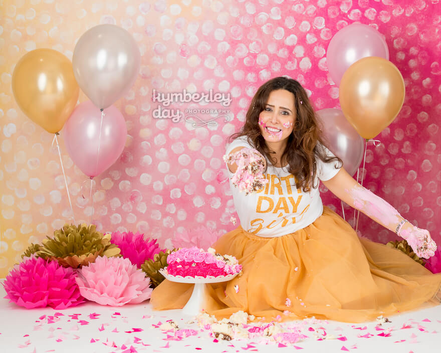 woman offering cake pink gold cake smash orange county