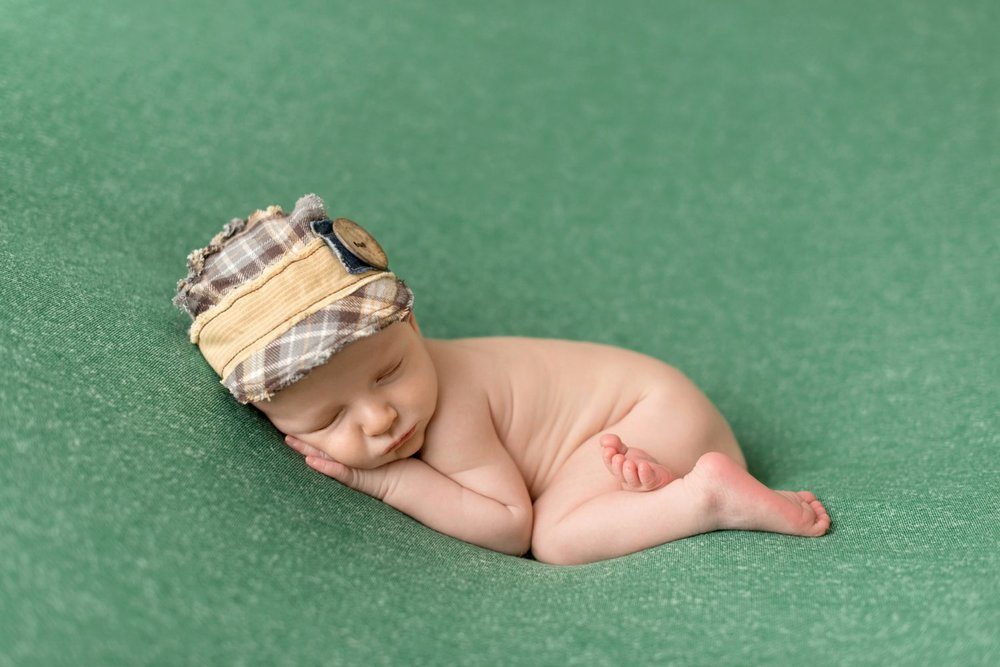newborn baby boy with plaid baseball cap on forest green blanket
