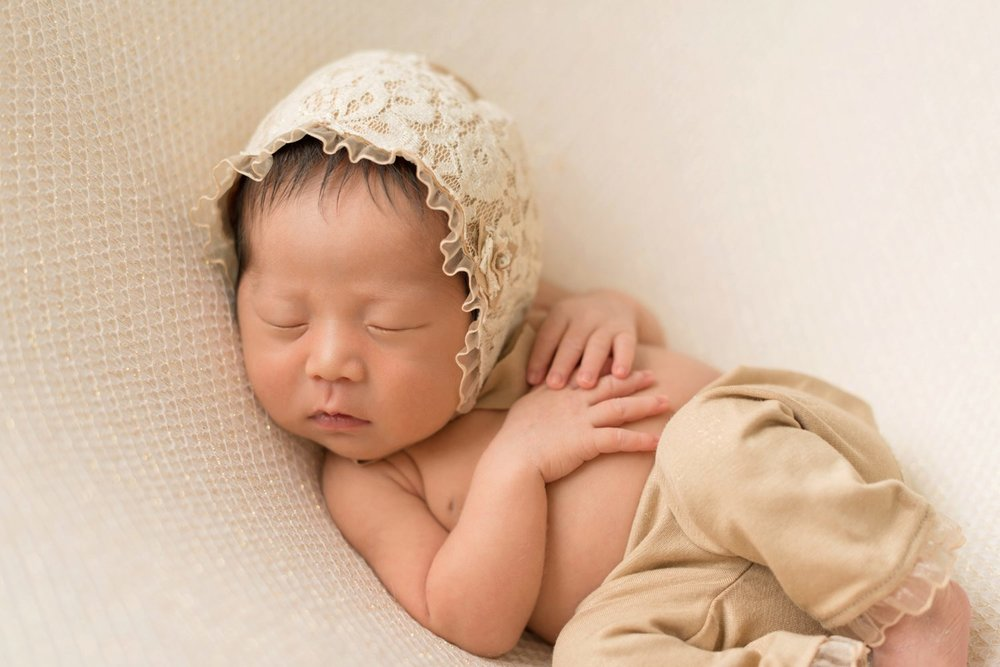 newborn baby with lace bonnet on cream and gold blanket