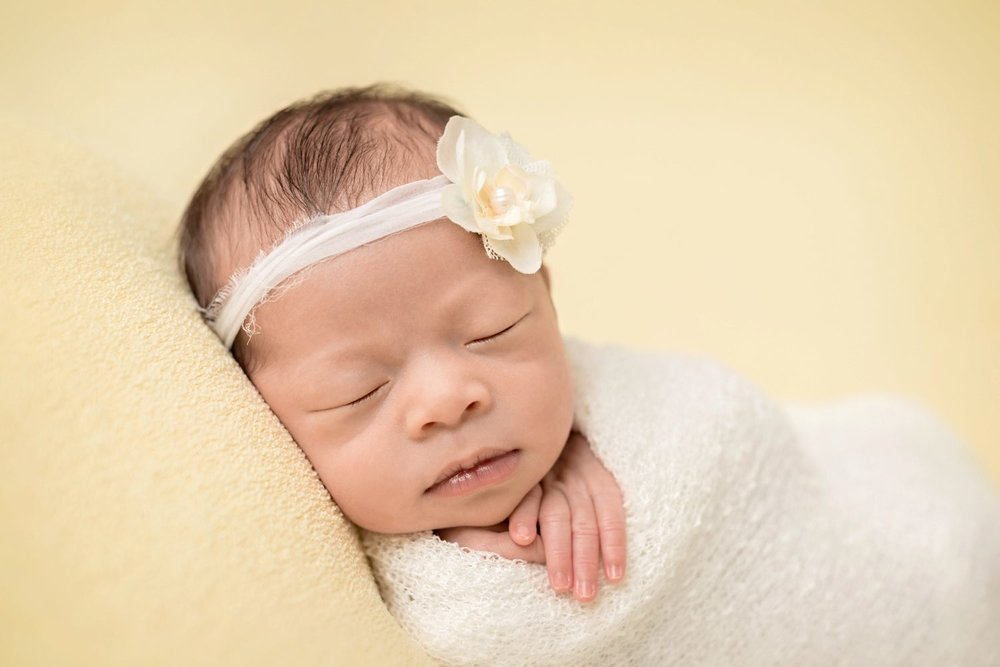 newborn twin baby girl on yellow backdrop in white wrap with yellow flower headband