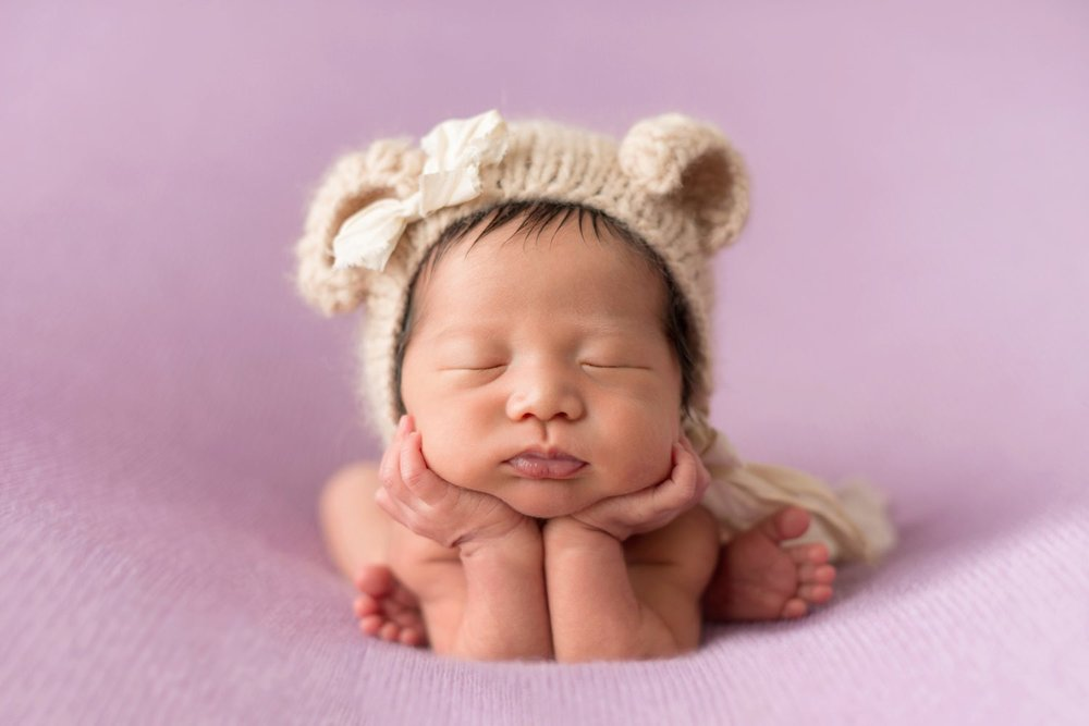 newborn baby girl wearing a bear hat with bow on purple blanket