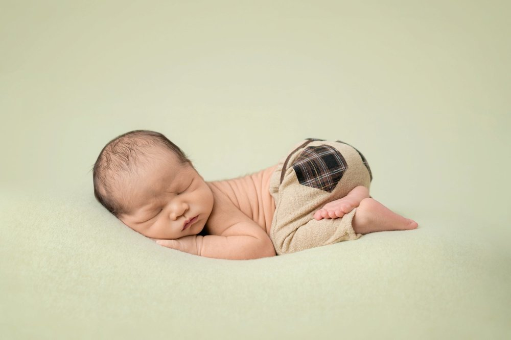 newborn baby boy in bum up pose in tan with plaid pants on sage blanket