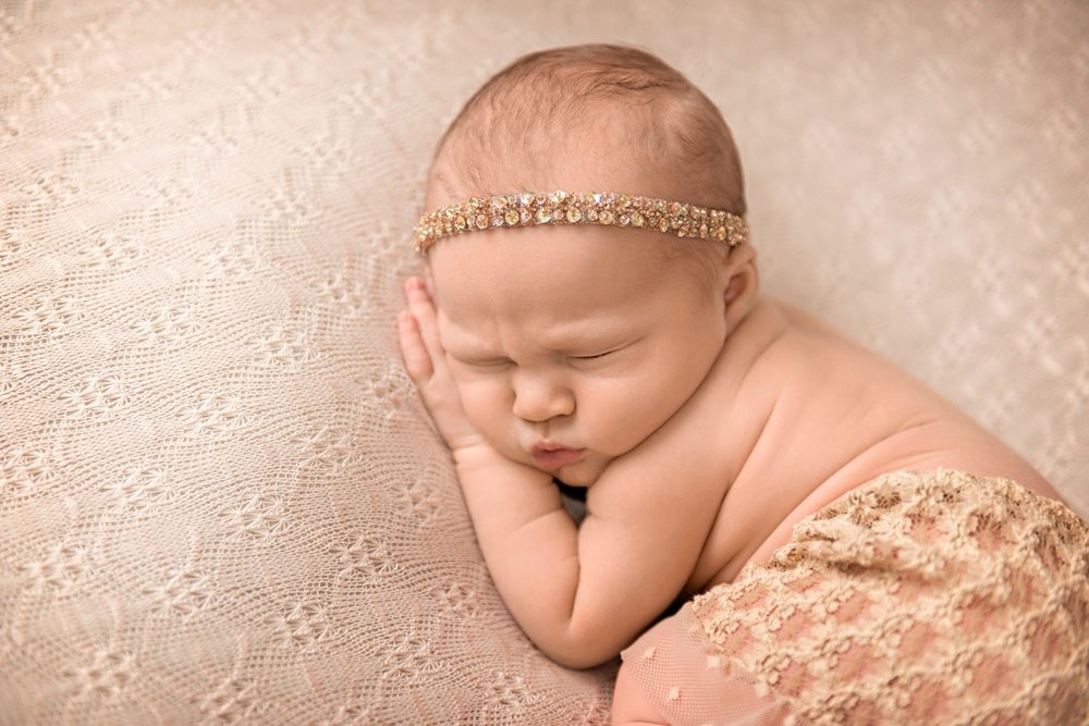 newborn sleeping with rhinestone headband and lace skirt