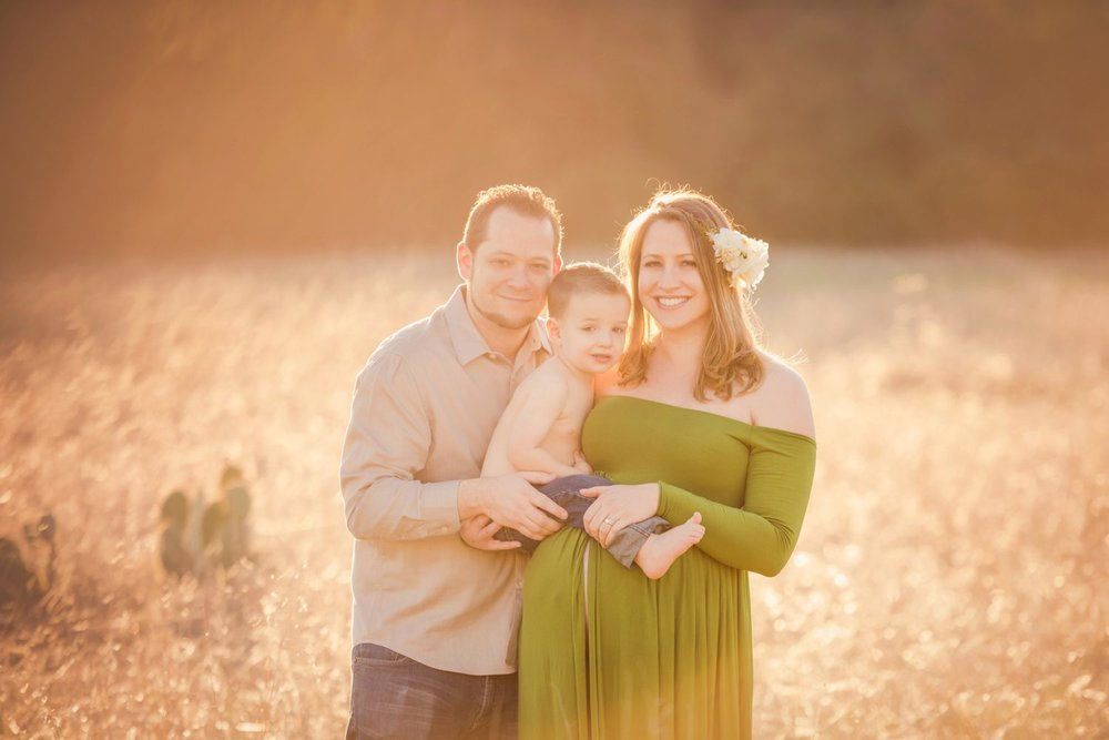 family maternity photo in golden field with green gown