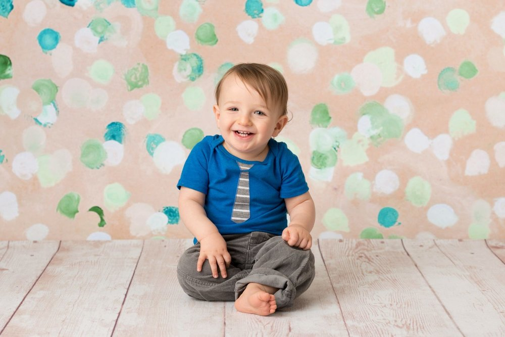 baby laughing in blue shirt with tie
