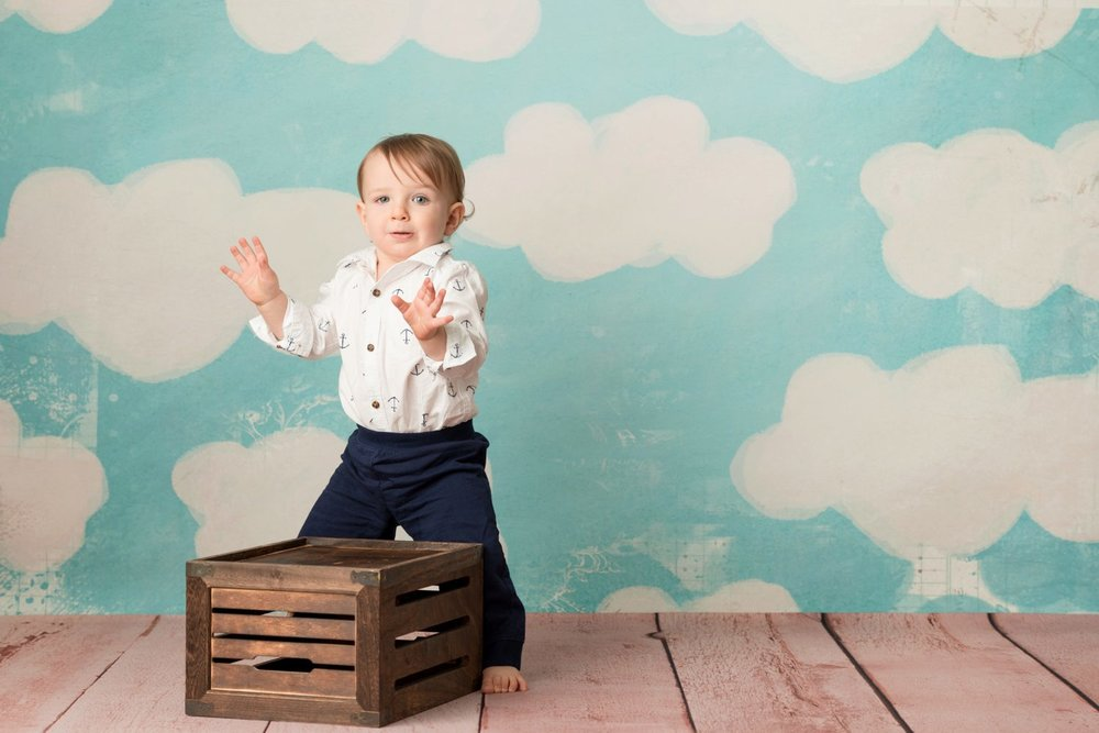 toddler standing up behind a crate
