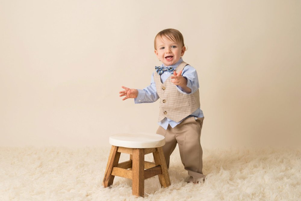 laughing clapping standing baby behind stool