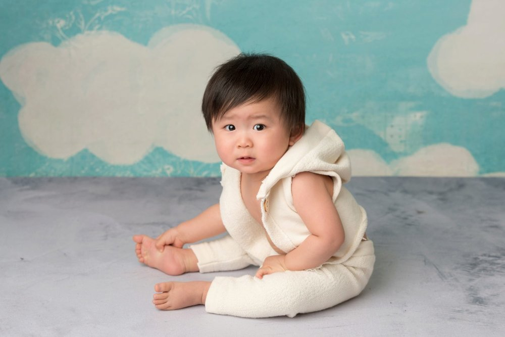 baby grabbing feet while sitting up in 2 piece outfit