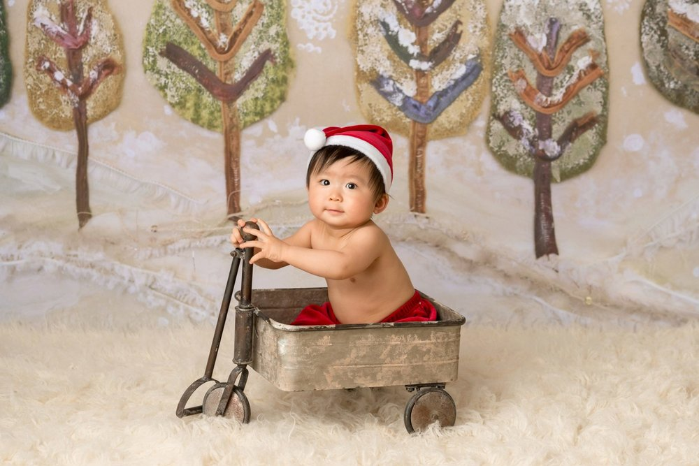 baby in santa outfit sitting in wagon