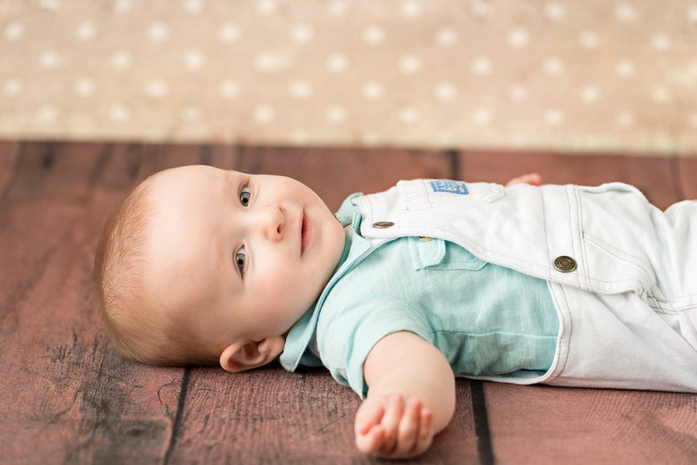 blonde baby boy in white overalls laying on floor