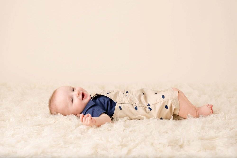 laughing baby on cream rug
