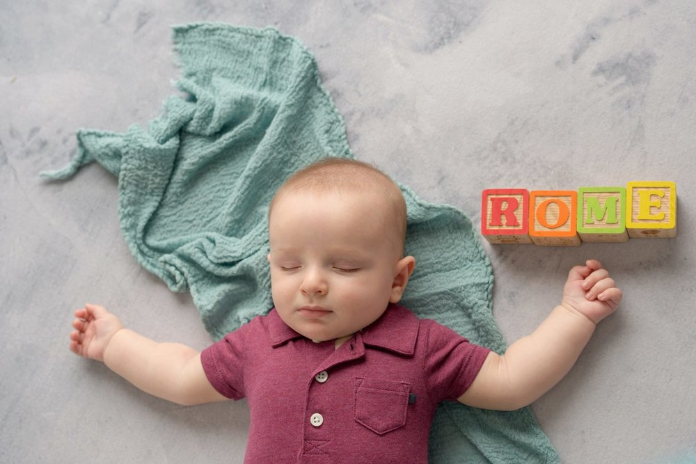 sleeping baby with name spelled in blocks