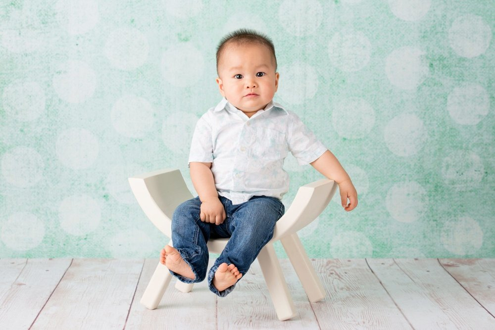baby boy sitting on white wooden chair