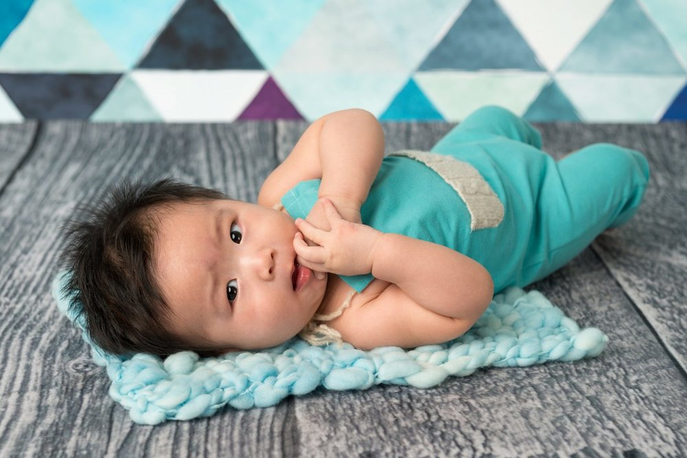 4 month old in blue romper on dark ground