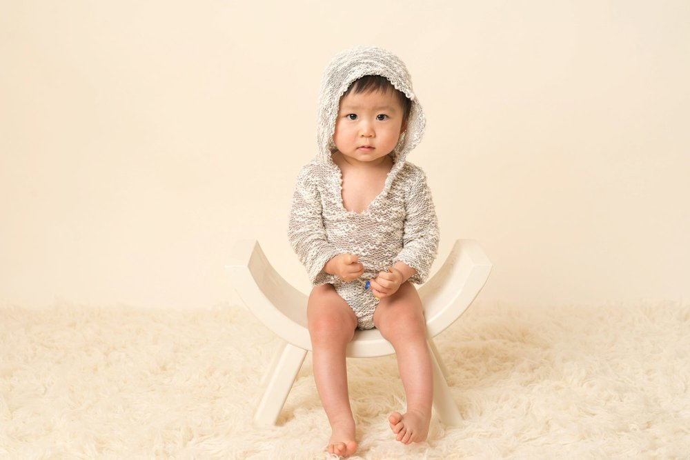 1 year old asian boy on cream in designer romper