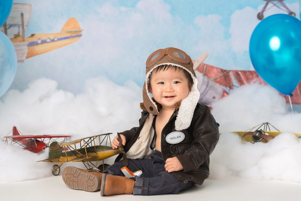 smiling birthday boy 1 year old aviator planes