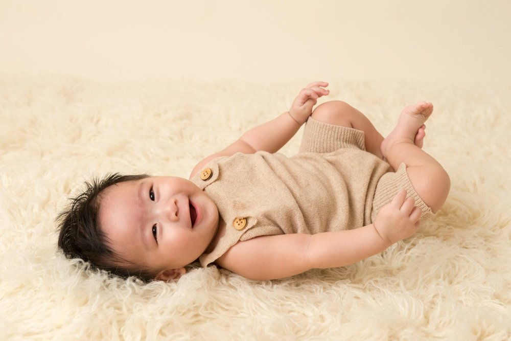 happy 4 month old boy in tan romper