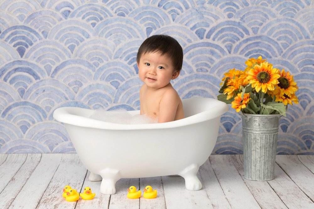 baby in bathtub with sunflower rubber duckies