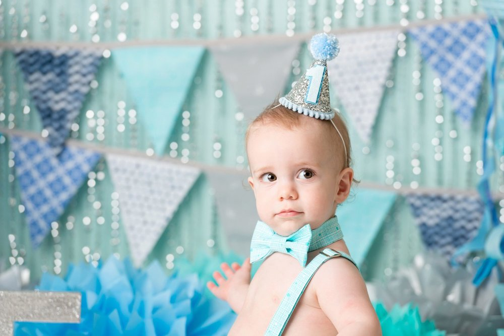 baby in party hat for first birthday blue set