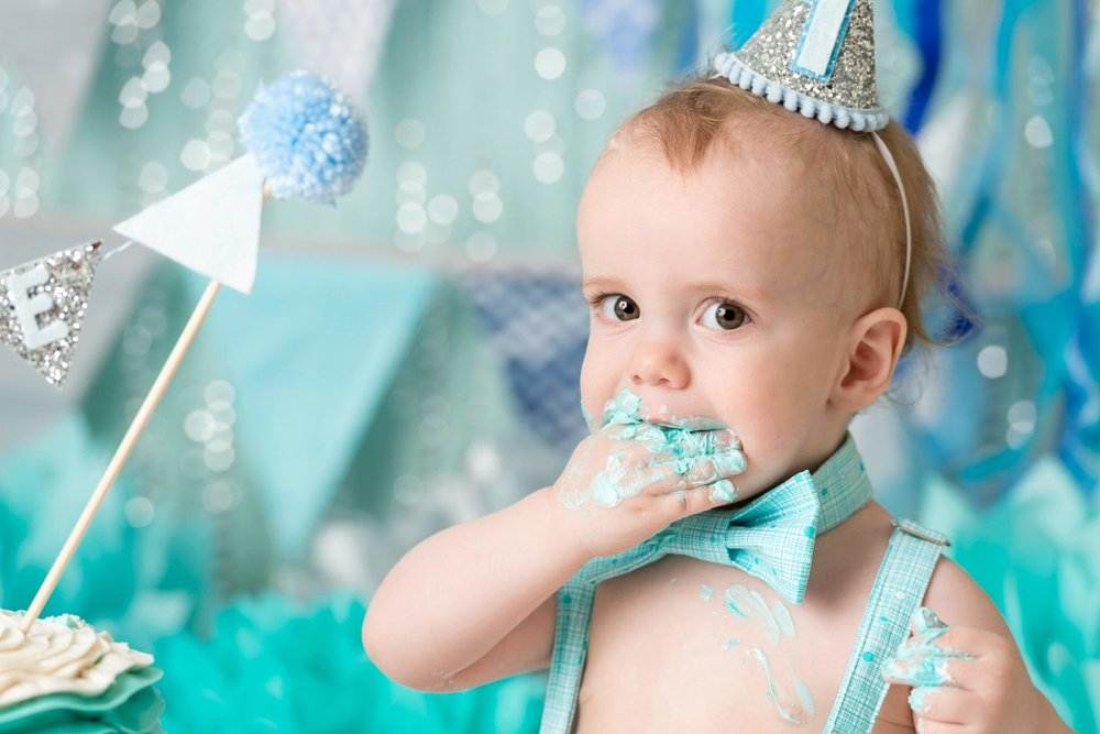 closeup of baby with frosting covered hand in mouth