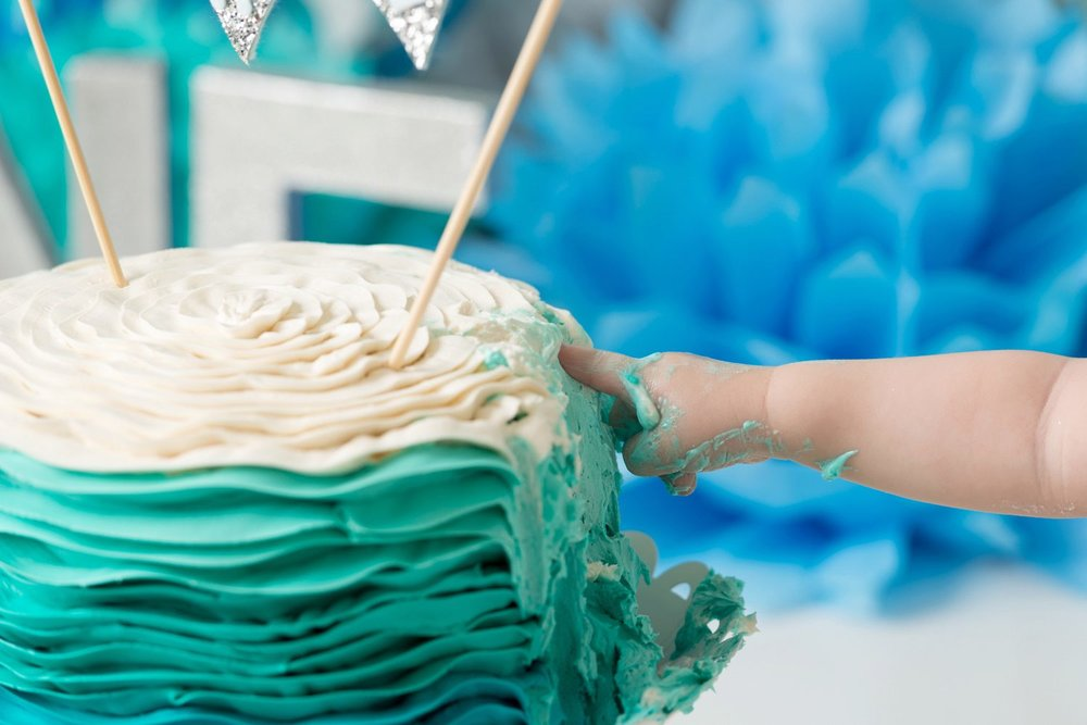 closeup baby finger in cake frosting cake smash