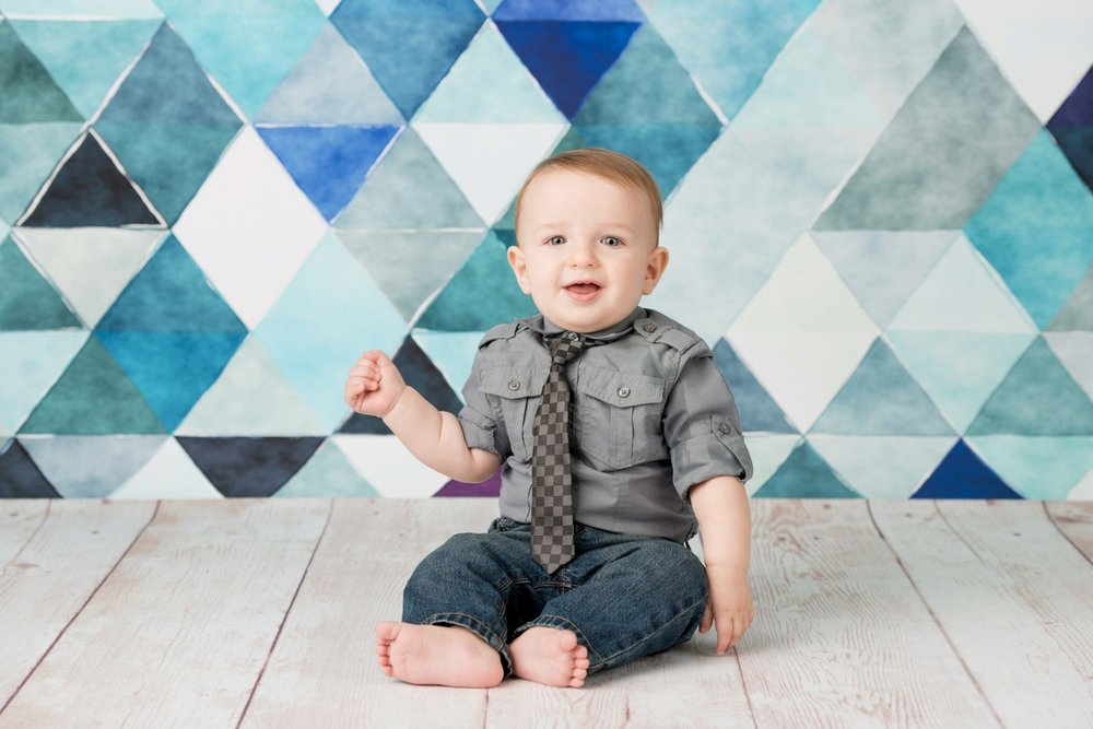 8 month baby sitting wearing tie on blue