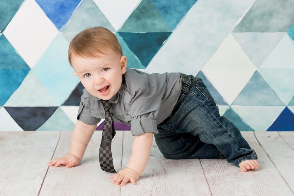 winking crawling baby boy on blue triangles and wood