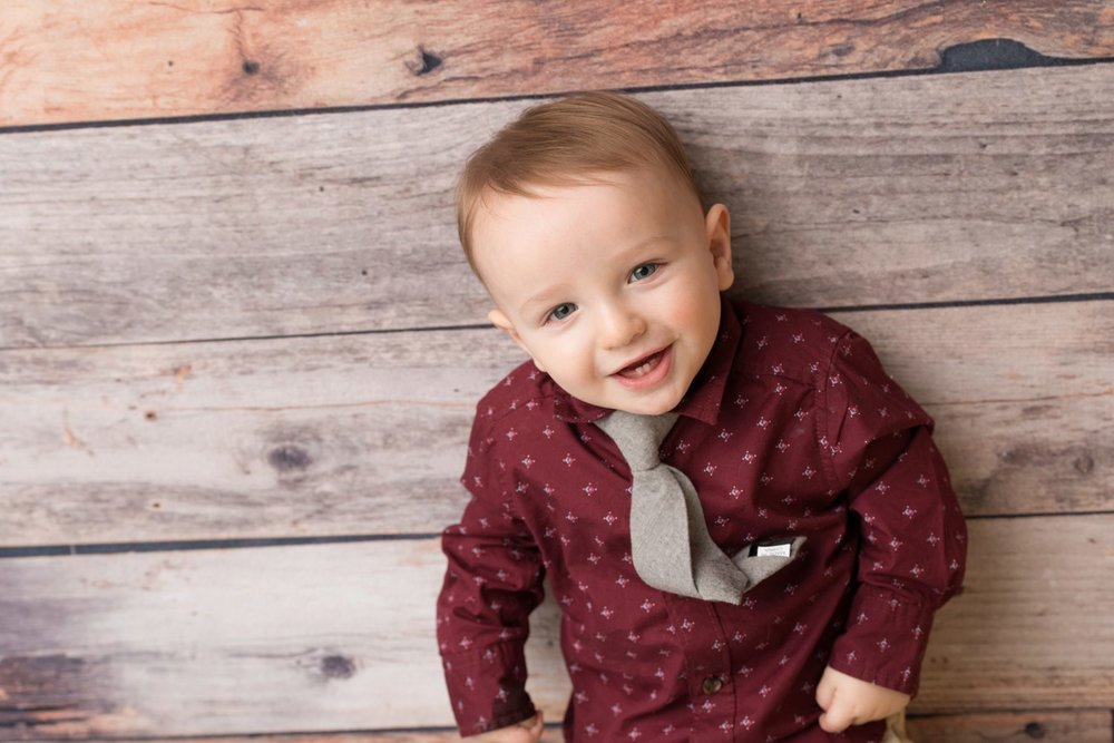 smiling baby wearing burgundy on wood