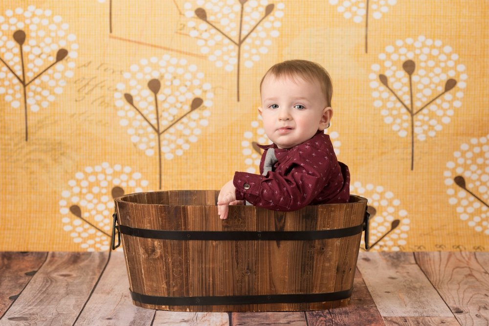 baby in wooden tub on yellow fall backdrop