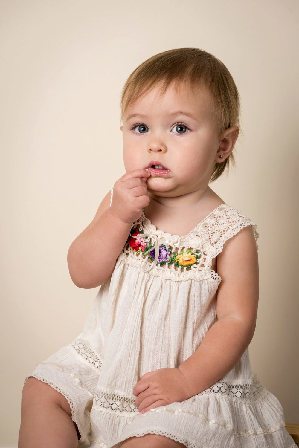 little girl grabbing lip wearing vintage dress on cream
