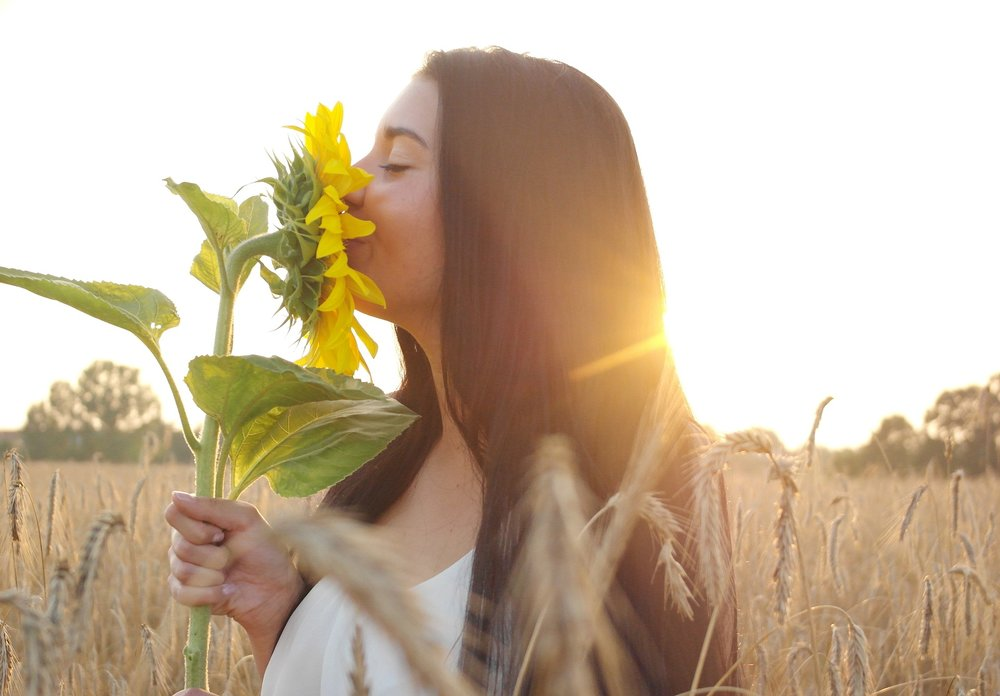 woman-in-sun-smelling-sunflower
