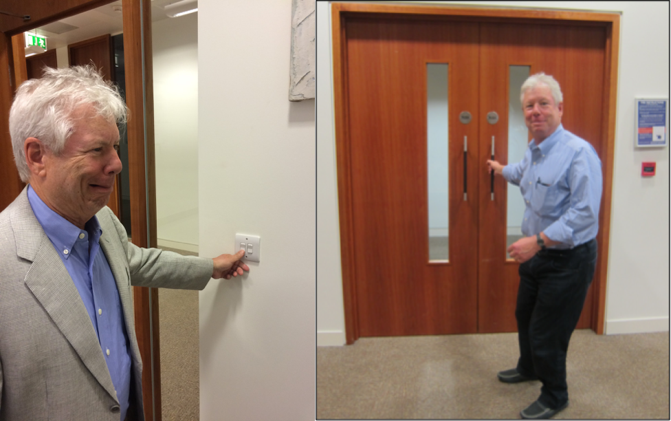 "Left: Thaler cringes about the fact that lights at the Booth London campus are switched on by counterintuitively pressing down not up. Right: Thaler poses with doors in Booth's London campus that have pull bars on both sides of the door, causing people to pull on the push side. Thaler was a big advocate of adding signs that note whether to push or pull above the handles, a ""real world"" application of his mantra, ""Make It Easy!"" Source: Linnea Gandhi."