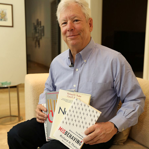 Thaler poses with his books  The Winner's Curse  (1993),  Nudge  (2008), and  Misbehaving  (2015). Source: The University of Chicago