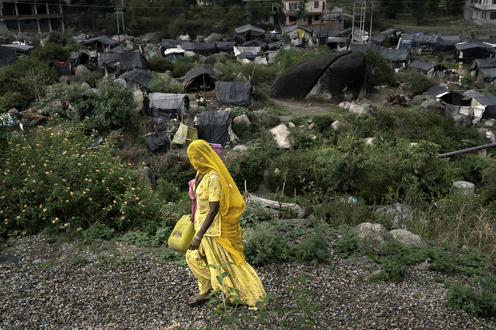 Throughout the world women and children are sent out each day to collect the water needed for use by their families. Here is one such woman leaving her shelter after a full day of work to gather the precious water in a slum in Dharamsala, India.  ©  Renée C. Byer